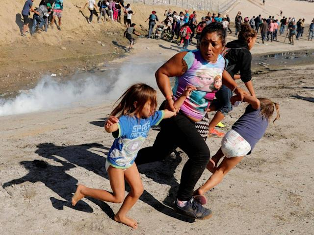 A migrant family from Honduras runs from tear gas fired by US border patrol at Mexico border (Reuters)