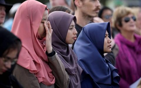 Members of the public react during the National Remembrance Service at North Hagley Park in Christchurch - Credit: AFP