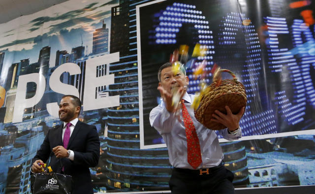 File Photo: Executives of the Philippine Stocks Exchange throw candies and coins to stock traders during the opening bell to signal the first trading day of 2018 at the financial district of Makati City, Philippines, Wednesday, Jan. 3, 2018. (AP Photo/Bullit Marquez)