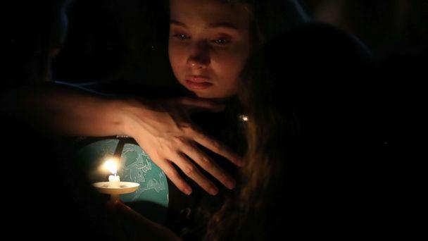 PHOTO: A young girl clutches a friend during candlelight vigil for victims of the mass shooting at Marjory Stoneman Douglas High School yesterday, at Pine Trail Park, Feb. 15, 2018 in Parkland, Fla. (Mark Wilson/Getty Images)
