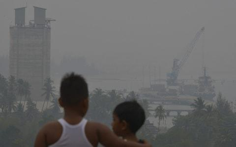 Children look into the haze in Indonesia's Aceh province - Credit: Chaideer Mahyuddin/AFP
