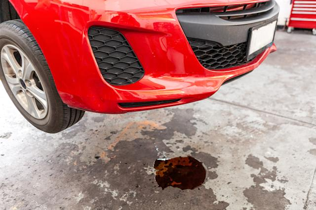 Concept of car oil leak depicted with red vehicle and puddle of oil underneath