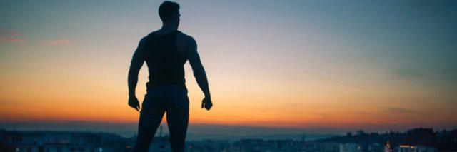 photo of man silhouetted against sunset sky in superhero pose, fists clenched and confident, looking out over city