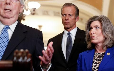 John Thune, the Senate Republican whip, watches as as Mitch McConnell, the Senate Republican leader, speaks on Tuesday - Credit: REUTERS/Tom Brenner