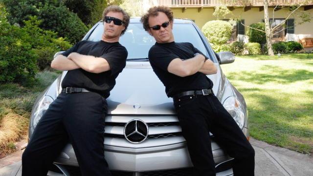 dos honbres vestidos de negros encima de un auto posando