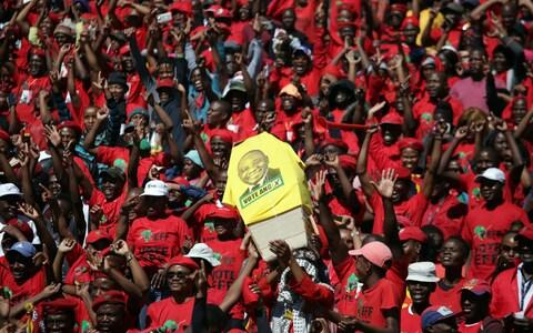 EFF supporters hold a mock coffin bearing the face of the ruling African National Congress (ANC) President Cyril Ramaphosa - Credit: AFP