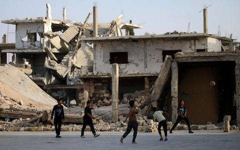 Children play football in front of a damaged building in a rebel-held neighbourhood of Deraa in southern Syria - Credit: AFP