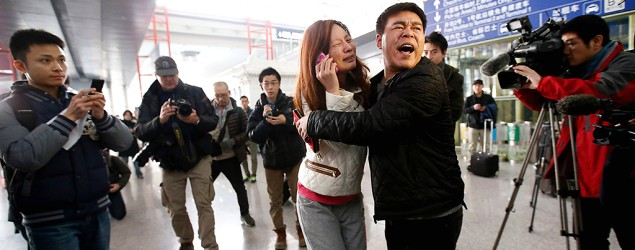 A relative (woman in white) of a passenger onboard Malaysia Airlines flight MH370 cries as she talks on her mobile phone at a Beijing airport. (Reuters)