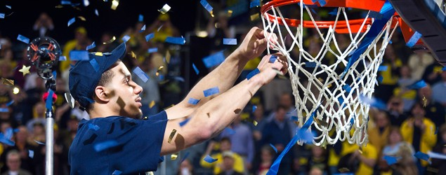 Michigan forward Jordan Morgan, a graduating senior, cuts down the net after an NCAA college basketball game against Indiana. (Tony Ding/AP)