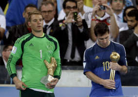 Germany's goalkeeper Manuel Neuer, recipient of the Golden Glove trophy, stands next to Argentina's Lionel Messi after he receive the Golden Ball trophy...