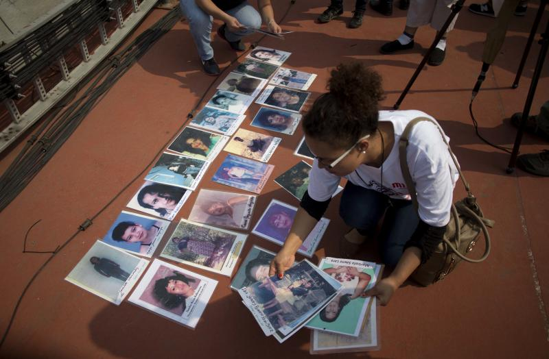 A woman lays pictures of missing Central American migrants during a march by mothers who are searching for their children, in Mexico City, Wednesday, Dec. 9, 2015. The caravan of women, mostly from Central America, are traveling through Mexico to search for their relatives who left for a better life in the U.S. but disappeared. (AP Photo/Eduardo Verdugo)